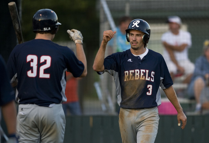 New Market's John Cable congratulates Brady Lloyd, right, after Lloyd scored after tagging up on a fly ball during fifth-inning action Wednesday night at First Bank Park in Strasburg. The Rebels lead the league in many offensive categories this season. Rich Cooley/Daily