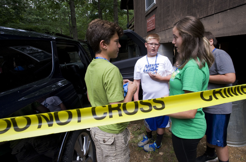 Shenandoah County Sheriff's Youth Office Leadership Camp participants Brayden Hovatter, 13, left, of Edinburg, Hayden Raley, 11, center, of Edinburg, and  camp counselor Megan Babcock, 15, right, of Woodstock, talk outside this Dodge Durango that was part of an evidence scene at the  camp at Shrine Mont in Orkney Springs last week.  Rich Cooley/Daily