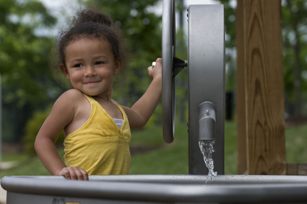 Aliyha Smith, 2, of Edinburg, cranks the wheel alongside a water feature at W.O. Riley Park in Woodstock recently. High humidity and  triple-digit temperatures will make water features and swimming pools popular places this week as people seek relief from the heat. Rich Cooley/Daily