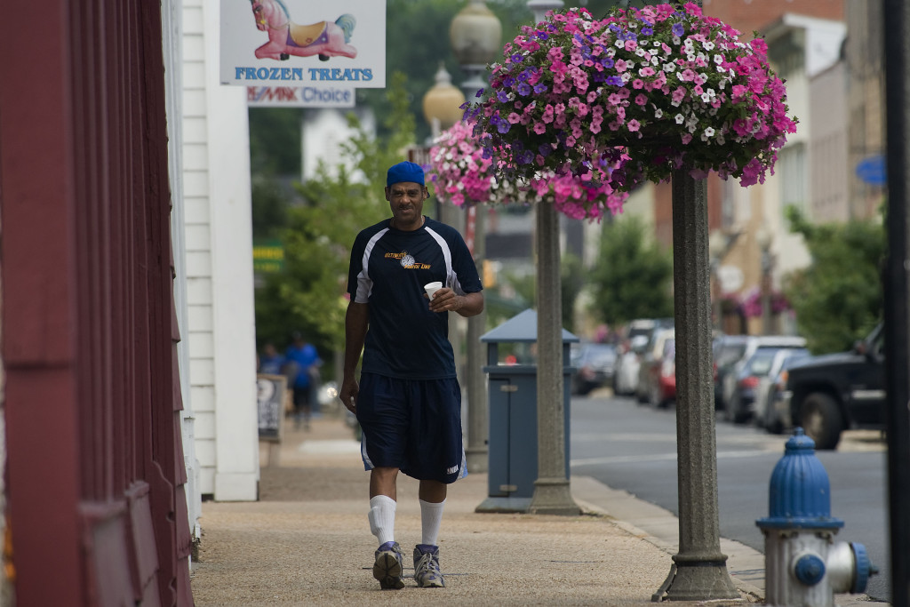 Charles Mitchell strolls past colorful flower baskets along East Main Street in Front Royal recently.  Rich Cooley/Daily