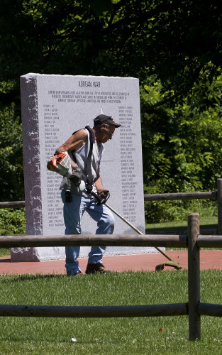 Ed Ellis uses a string trimmer as he works his way around the brick work at the Korean War monument in Jim Barnett Park.  Rich Cooley/Daily