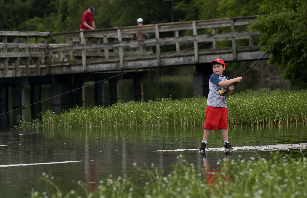 Chip Newcome, 8, of Winchester, fishes at Lake Frederick on a recent summer afternoon.  Rich Cooley/Daily