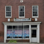 The Brill's Grocery sign hangs over what was once a grocery store and is now an abandoned building in downtown Strasburg. Town Council will hold a public hearing Tuesday on demolishing the building and a nearby taxi stand building.  Jake Zuckerman/Daily