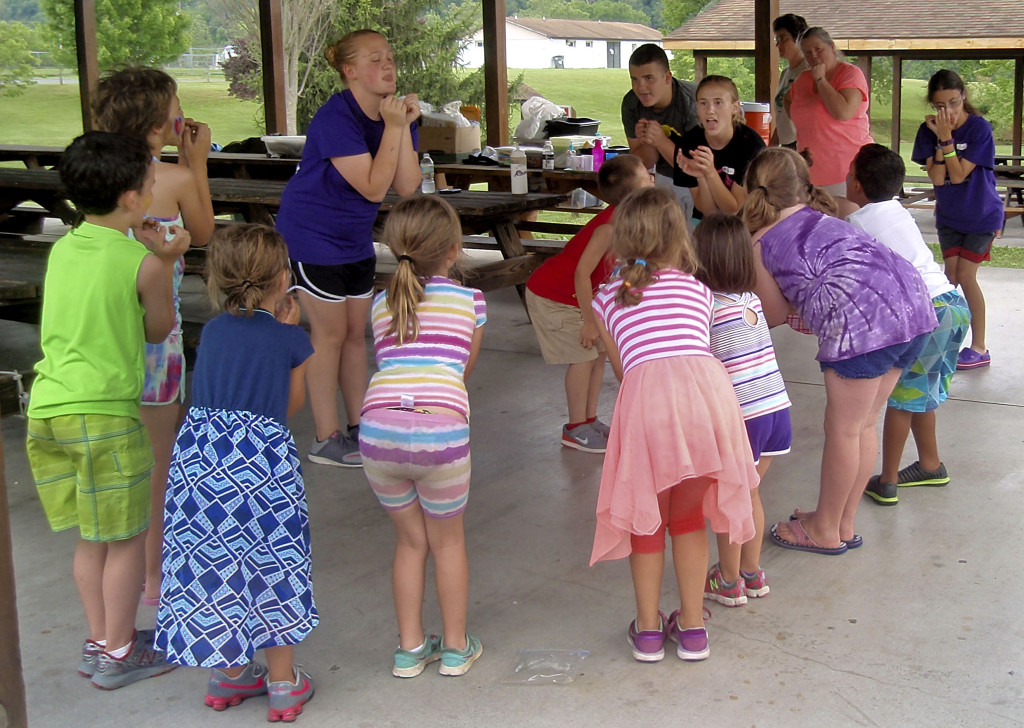 Anna Rankin, center, a Shenandoah County 4-H teen leader from Strasburg, leads kids in a group song as part of the Strasburg Cloverbud 4-H day camp held June 21-23 at the Strasburg Town Park. Courtesy photo