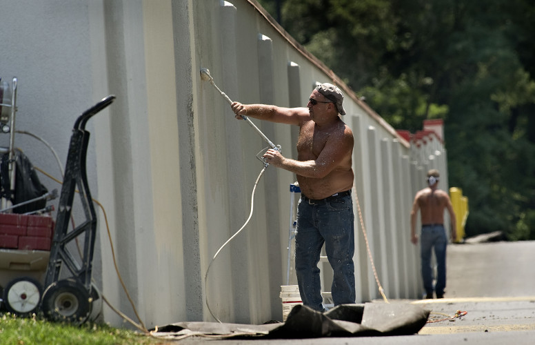 Jim Reinheimer, owner of American Home Pride LLC in Winchester, paints a long stretch of wall outside Bing Crosby Stadium in Front Royal.  Rich Cooley/Daily