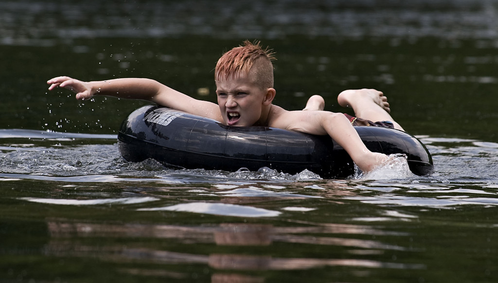 Logan Parson, 9, of Front Royal, floats on an inner tube along the Shenandoah River in Front Royal on a hot summer afternoon.  Rich Cooley/Daily