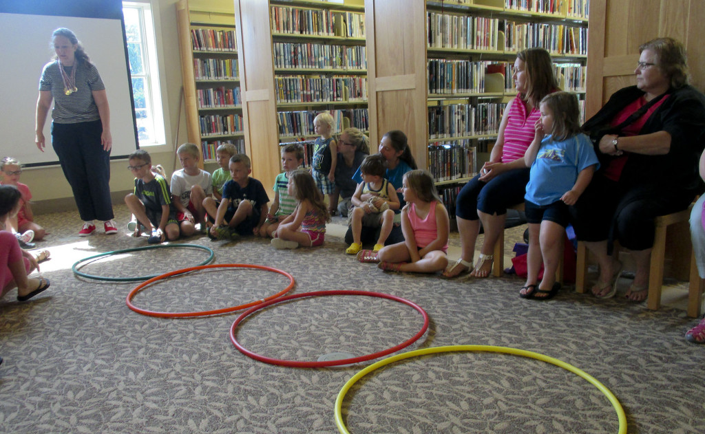 """Wendy Whitford, upper left, band and orchestra teacher at North Fork Middle School, and Joanne Thompson, an instructional assistant at North Fork Middle School, teamed up to present """"O-utstanding O-lympics"""" at the New Market Area Library using hula hoops as part of its summer reading program. Children and adults listened and participated in stories with indoor Olympics-inspired games. Photo courtesy of Karen Whetzel"""