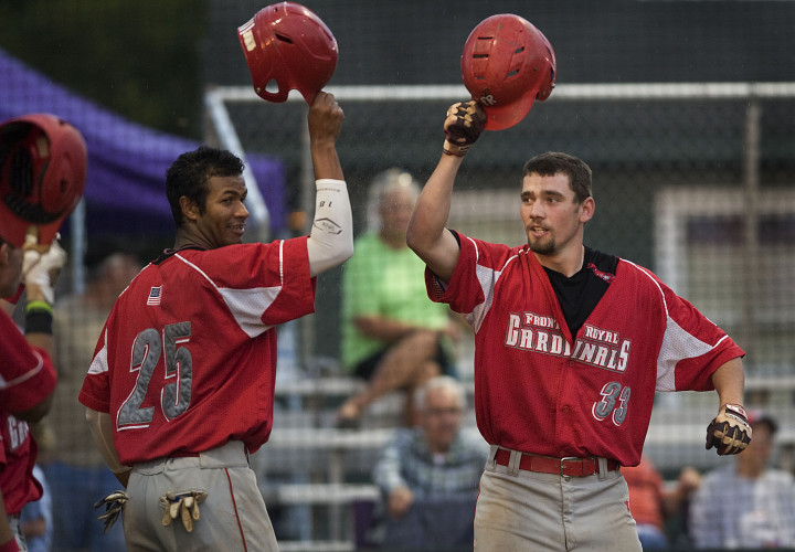 Front Royal's Zac Wiley, right, connects helmets with teammate Bernabe Camargo after Wiley's two-run homer on July 12 at First Bank Park. Wiley and the Cardinals play Winchester today in the playoffs.  Rich Cooley/Daily file