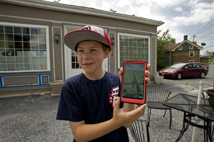 Sean Voehmer, 12, of Strasburg, holds up his phone with the Pokemon Go game on it outside the former Holy Moly Donut shop at the corner of King and Massanutten streets in Strasburg.  Rich Cooley/Daily