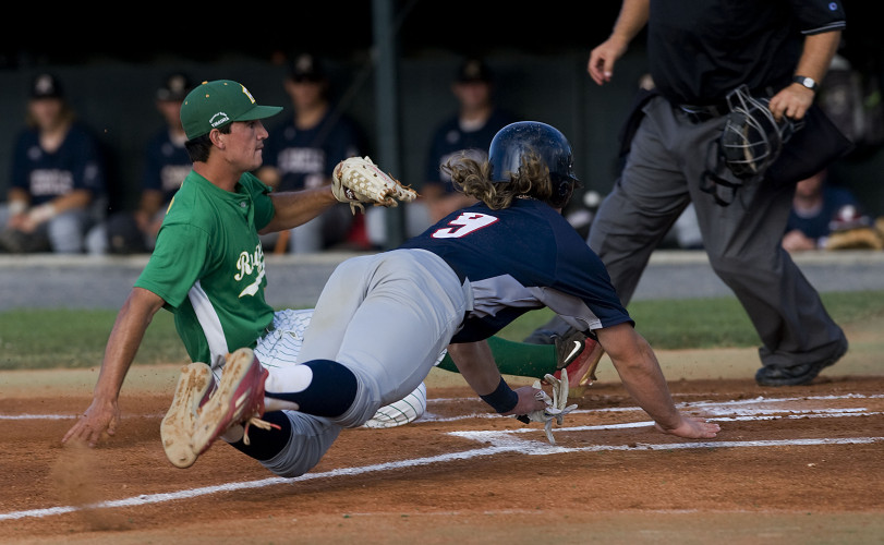 New Market's Brendan Donovan dives head first into home plate after a wild pitch by Winchester's Dillon Brown during the first inning of Thursday night's game at Bridgeforth Field in Winchester. Donovan was safe on the play. Rich Cooley/Daily