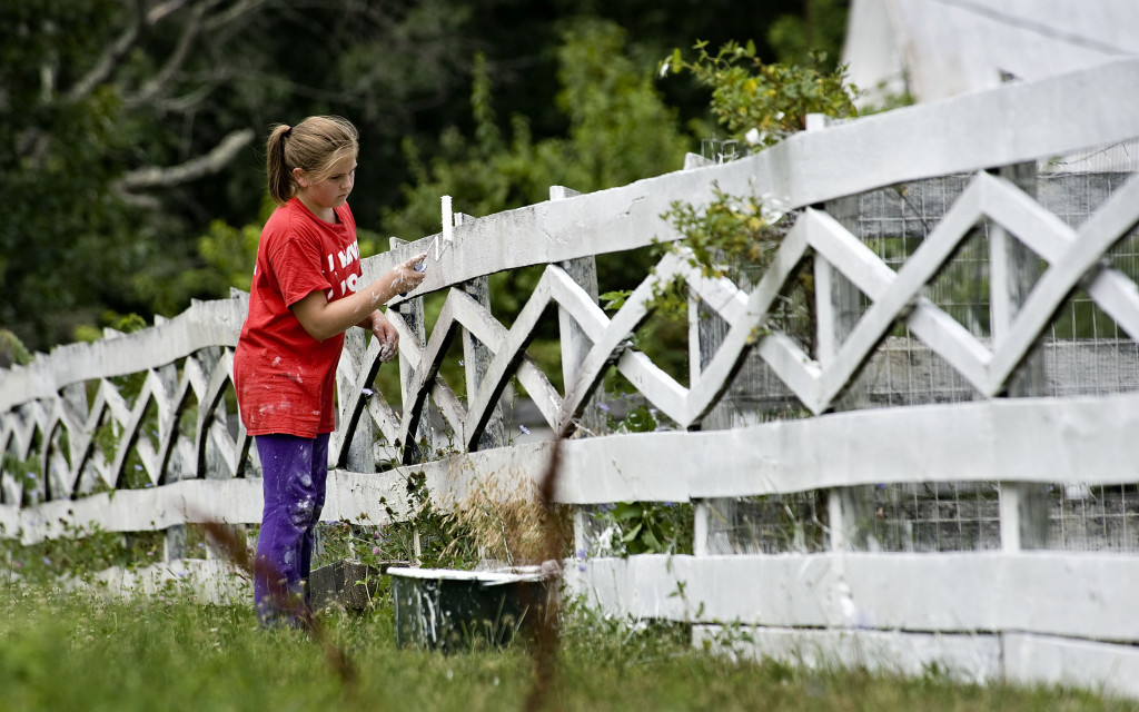 Avery Lunde, 12, of Middletown, paints a line of board fence outside a farm off Reliance Road east of Middletown recently.  Rich Cooley/Daily