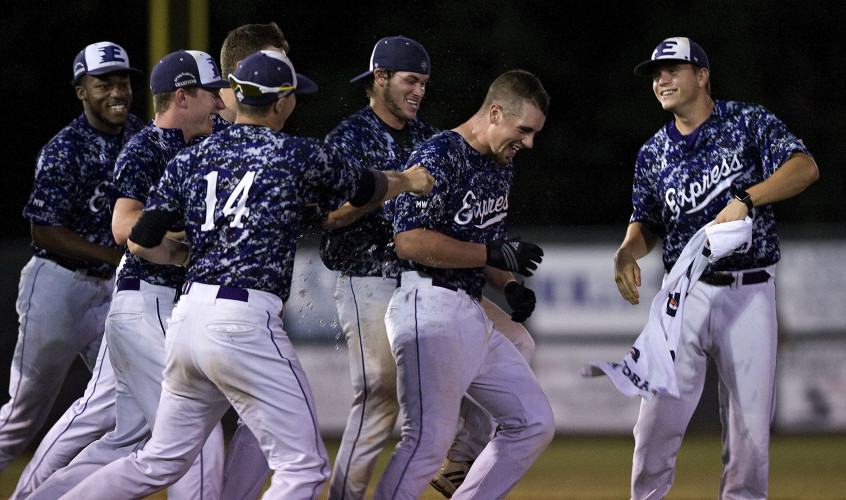 Members of the Strasburg Express mob Brandon Quaranta after he hit a double that drove in the winning run to defeat Waynesboro 3-2 in the ninth inning Friday night at First Bank Park. Rich Cooley/Daily