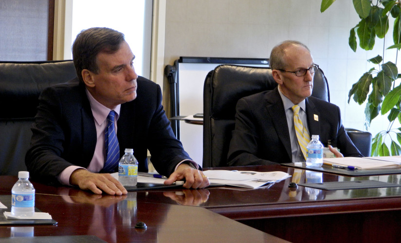 Virginia senator Mark Warner, left, and Mark Merrill, president and CEO of Valley Health System, listen Monday to officials with the Northern Shenandoah Valley Substance Abuse Coalition speak during a roundtable discussion on opiate addiction. Rachel Mahoney/Daily