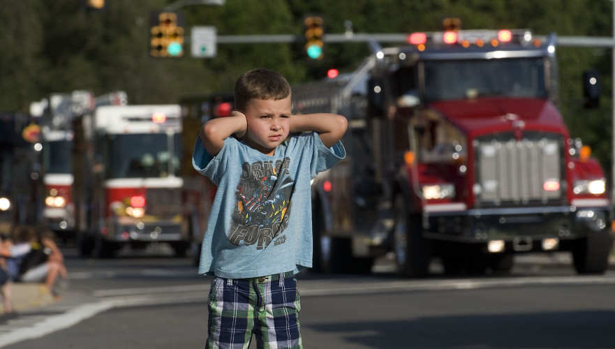 Logan Morris, 5, of Front Royal, covers his ears as fire trucks blast their sirens along a stretch of Commerce Avenue during Front Royal Fire Department's Firefighters Parade held Wednesday night. The Firefighters Carnival continues nightly through July 23, and today will feature a fireworks display. Rich Cooley/Daily