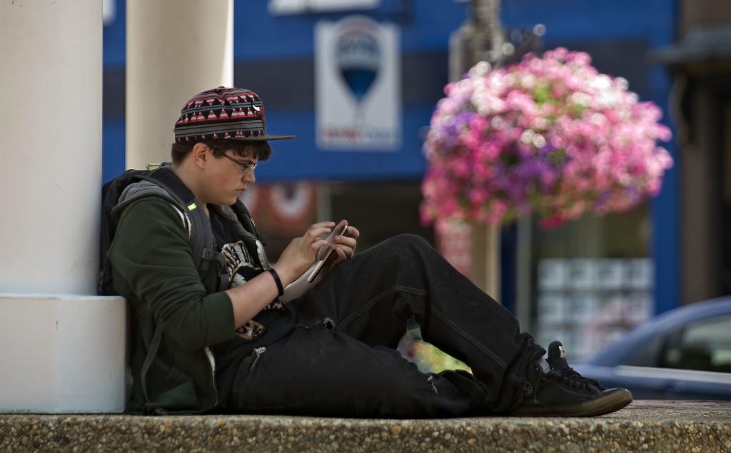 Devon Maness, 16, of Front Royal, plays on the Pokemon Go app outside the gazebo on East Main Street in Front Royal on a sunny afternoon. Rich Cooley/Daily