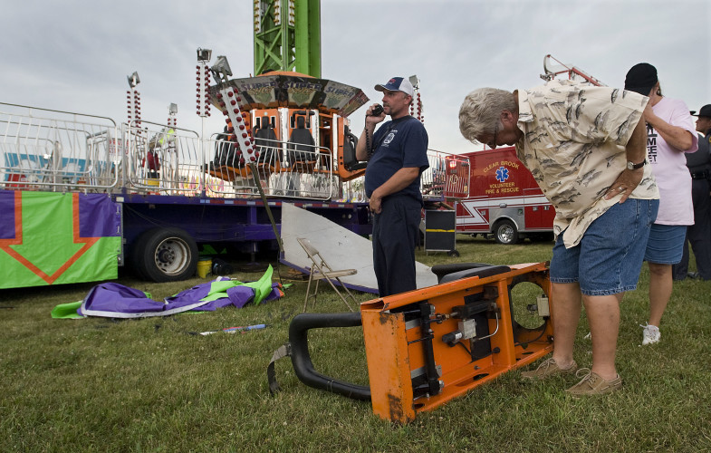 A spectator looks over a seat that fell Monday night from the Super Shot ride at the Frederick County Fair.  Rich Cooley/Daily