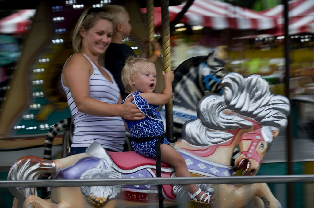 Kasey Mowery, of Romney, West Virginia, holds her daughter  Elizabeth, 15 months, as the pair ride the merry-go-round at the Frederick County Fairgrounds this week.  Rich Cooley/Daily