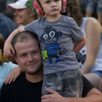 Russ Hoffman and his son Kaleb, 5, of Inwood, West Virginia, watch the Monster Truck Show on Tuesday night at the Frederick County Fairgrounds. Rich Cooley/Daily