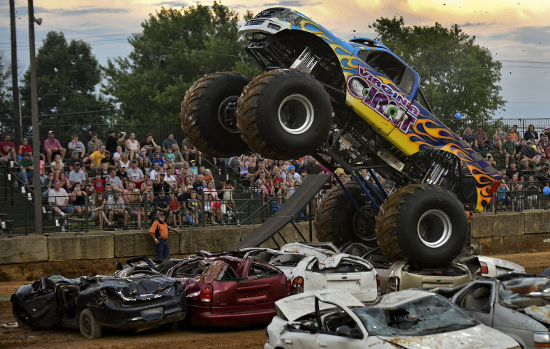 The Virginia Giant, driven by Diehl Wilson, of Winchester, goes high as it crushes a row of cars during the Monster Truck Show on Tuesday night at the Frederick County Fairgrounds. Rich Cooley/Daily