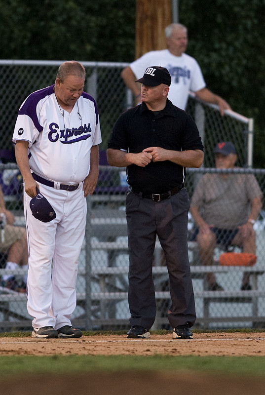 Strasburg manager Butch Barnes talks with the umpire on a foul ball call during playoff ation against Purcellville on July 29 at First Bank Park.   Rich Cooley/Daily file