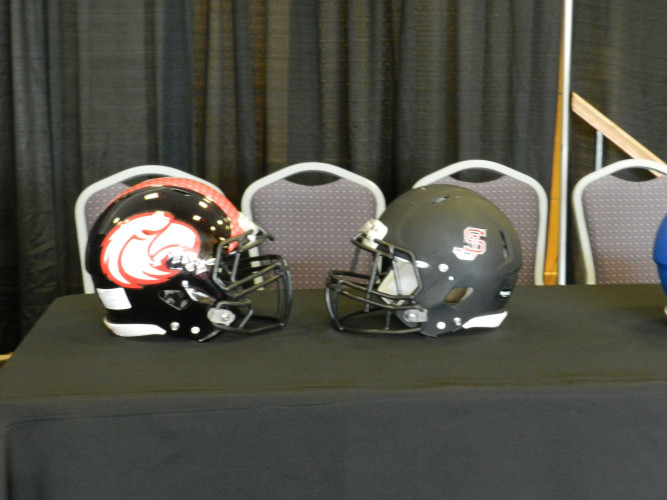 Helmets for Stonewall Jackson and  East Rockingham are displayed at a press conference at JMU on Thursday. Stonewall Jackson and East Rockingham will play at JMU on Oct. 15. The game will be part of the Shenandoah Valley Football Classic. Tommy Keeler Jr./Daily