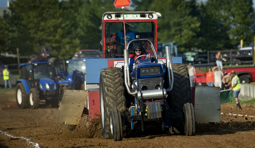 Tim Dawe, of Winchester, drives a Ford tractor owned by Rick Surface, of Berryville, down the track Thursday during the Truck and Tractor Pull at the Warren County Fairgrounds. Dawe was competing in the 6,000-pound classic class. The fair continues today, featuring the Lawn Mower Pull at 6 p.m. and the 4-H Livestock Auction at 7 p.m. Rich Cooley/Daily
