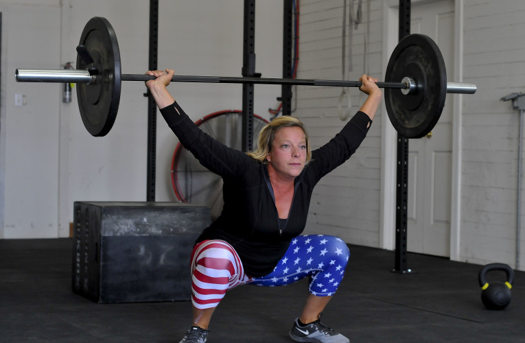 Tammy Dellinger, owner of Battlefield Fitness, Strasburg's newest CrossFit gym, performs a snatch, a signature Crossfit workout.  Jake Zuckerman/Daily