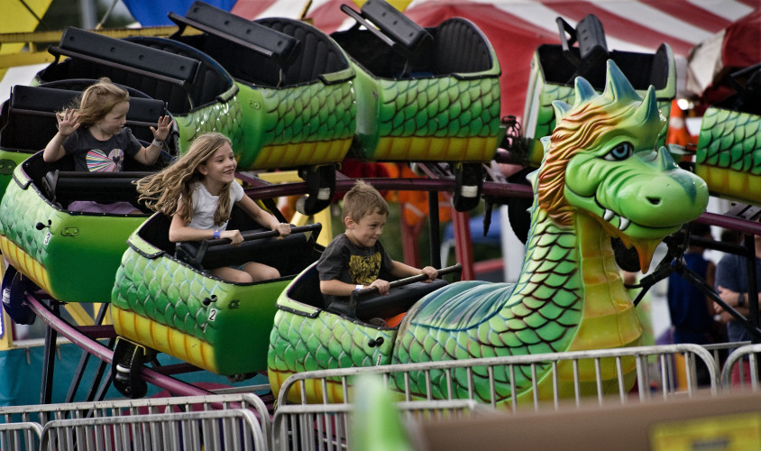 Children ride the Dragon Wagon during the Warren County Fair on Friday night under dark skies and some light rain. The fair has its final day today and will feature Monster Trucks at 6 p.m., the Greased Pig Contest at 7:30 p.m. and performances by the Beach Bumz Band at 7:30 p.m. and 9 p.m. Rich Cooley/Daily