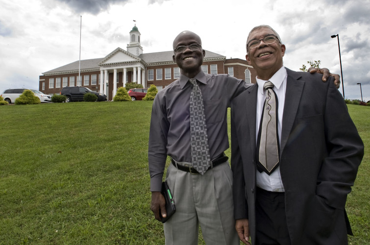The Rev. William P. Kilby, left, of Liberia, stands with his cousin, the Rev. James M. Kilby, of Front Royal, on the lawn of Warren County Middle School in Front Royal. The Kilbys recently met for the first time and have been visiting area landmarks recalling efforts in the 1950s to integrate students in public schools. The school was formerly Warren County High School, and James Kilby was one of the first black students to attend it in 1959.  Rich Cooley/Daily