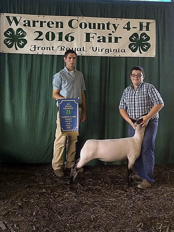 Ryan Atkins, right, won the Grand Champion market lamb contest at last week's Warren County Fair.  At left is Cody Boden, contest judge. Courtesy photo.