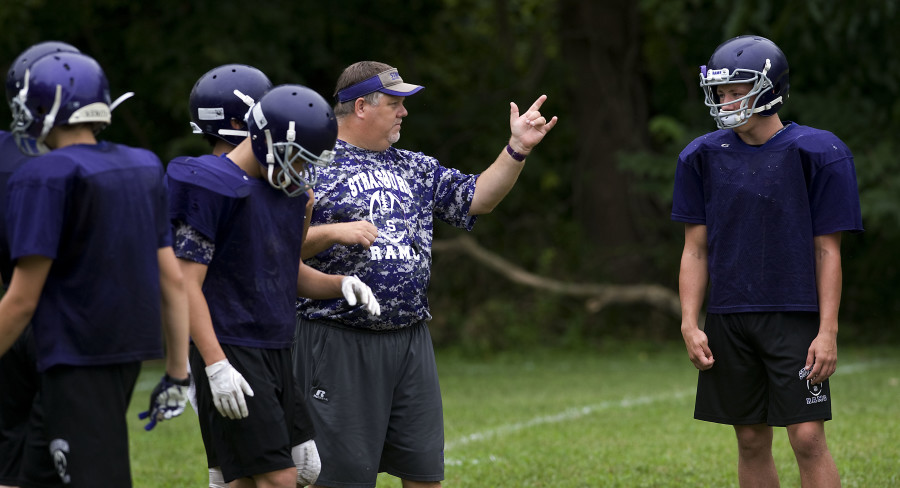 Strasburg coach Mark Roller works with his offensive unit during a recent practice.  The Rams have a young and inexperienced squad this season. Rich Cooley/Daily
