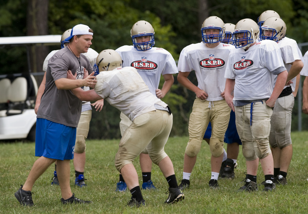 Central assistant coach Rowdy Hoover works with linemen during a recent practice. The Falcons will have a young squad this season with 24 sophomores on the team. Rich Cooley/Daily