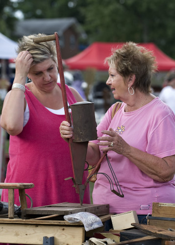 Stacey Schunann, left, of Germantown, Maryland, and her mother Ruta Schunann, of Bridgeville, Delaware, mull over purchasing an old corn planter Friday at Fishers Hill. The Yard Crawl officially begins today.  Rich Cooley//Daily
