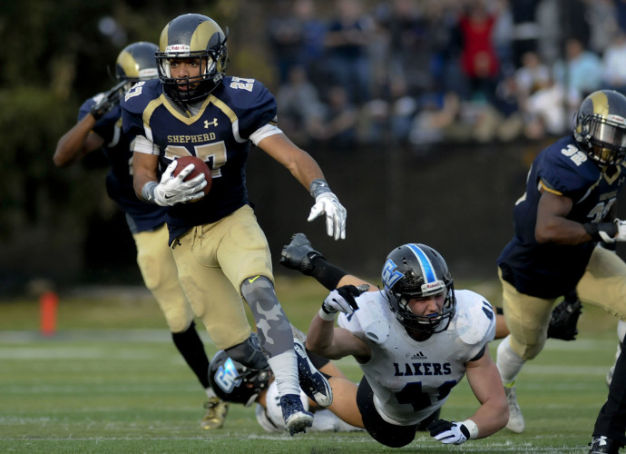 Shepherd defensive back C.J. Davis (27) evades a tackle attempt by Grand Valley State's Nick Keizer (41) and turns a 29-yard interception into a touchdown during the fourth quarter.   Journal Photo by Ron Agnir