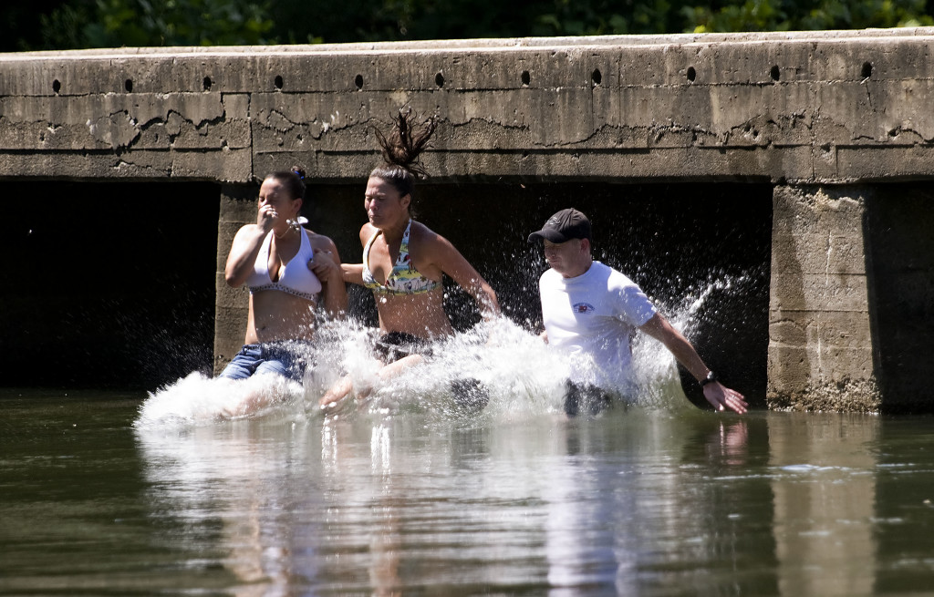 From left, Liz Knight-Suddarth, of Mount Jackson; Melissa Brecht, of Edinburg; and Brian Suddarth, of Mount Jackson, plunge into the Shenandoah River after a leap off the bridge at Chapmans Landing near Edinburg on Tuesday afternoon. Temperatures climbed into the mid-90s Tuesday.  Rich Cooley/Daily