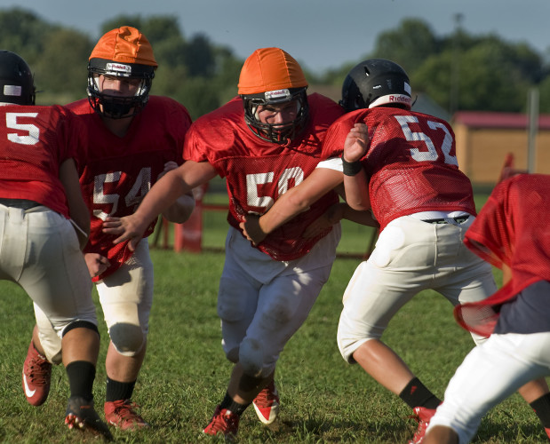 Stonewall Jackson's Chance Stroop fights through a blocker during practice. Rich Cooley/Daily