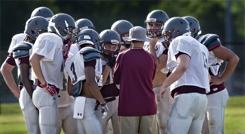 Warren County head coach Steve Crist huddles with his offensive players during a recent practice. Rich Cooley/Daily