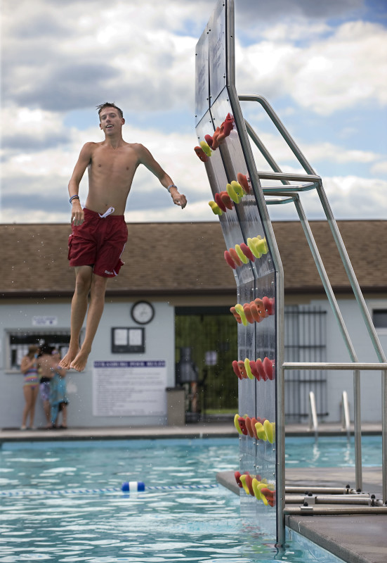 Nathan Hershey, 17, of Strasburg, leaps off a 12-foot pool climbing wall Monday at Strasburg's town pool. The apparatus, which was purchased to replace a former diving board, cost the town $17,000 and was put into use over a week ago.  Rich Cooley/Daily