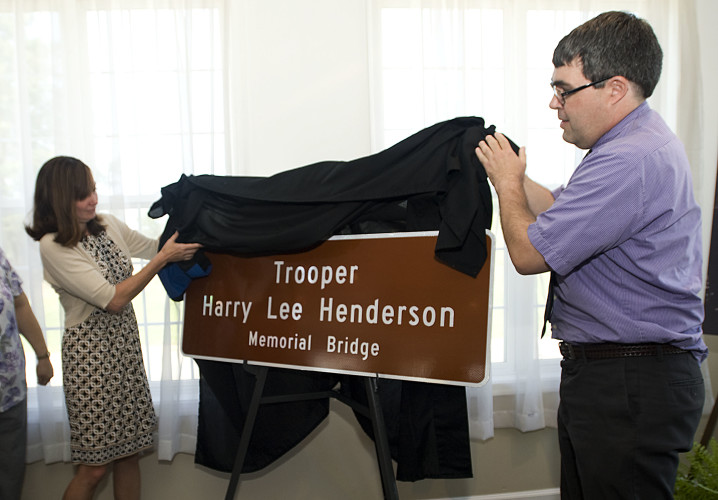 Mary Henderson, left, of Baltimore, Maryland, and her brother Michael Henderson, of Richmond, unveil the Trooper Harry Lee Henderson Memorial Bridge sign at the Front Royal Country Club on Tuesday. Rich Cooley/Daily