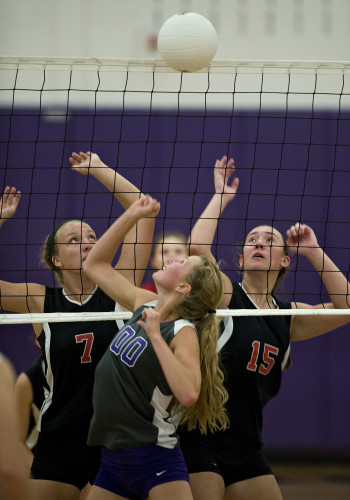 Strasburg's Cassie Cooper goes up to block a shot that rolled over the net as Stonewall's Emily Ball, left, and Israel Blank right, look on during a volleyball match Tuesday night in Strasburg. Rich Cooley/Daily