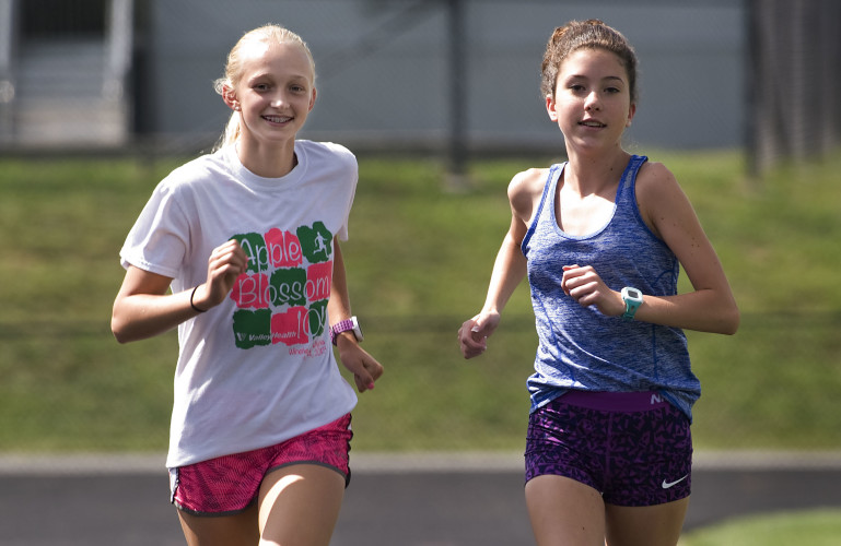 Sherando's  cross country runners Camryn Ubert, left, and Olivia Couillard, right, take a warm up lap around the track at Sherando High School during a recent practice. The sophomores are the top runners and leaders for the team this year.  Rich Cooley/Daily