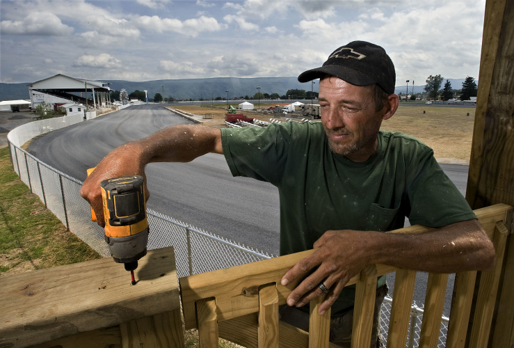 Bob Wilkins, owner of Bob's Builders located in Baker, West Virginia, installs one of the two camera houses along the edges of the harness racing track at the Shenandoah County Fair on Thursday. The fair will officially open today featuring a greased pig contest at 7 p.m.  Rich Cooley/Daily