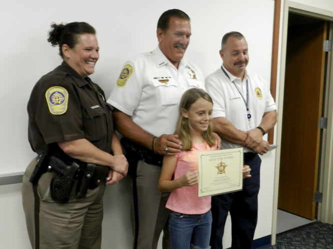 Sarah Ryan, an 11-year-old from Stephens City, holds up her Gold Star Award given to her by Frederick County Sheriff Lenny Millholland, center, with deputy Jeanine Bowers, left, and Frederick County Fire Chief Dennis Linaburg. Rachel Mahoney/Daily