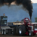 Jason Bowers, of Maurertown, blows a plume of smoke as he competes in the tractor pull during the Shenandoah County Fair on Saturday night. Rich Cooley/Daily