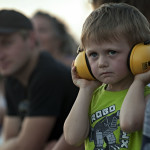 Lukas Gochenour, 3, of Woodstock, puts on his ear protection as he watches the tractor pull Saturday night at the Shenandoah County Fairgrounds. Rich Cooley/Daily