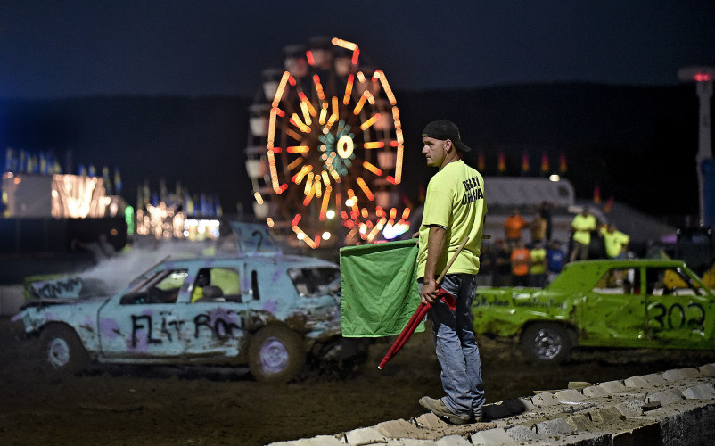 Kevin Shipe, a Toms Brook Volunteer Fire Department member, serves as a derby official during the stock demolition derby Monday night at the Shenandoah County Fairgrounds. Thirty cars participated in the event.   Rich Cooley/Daily