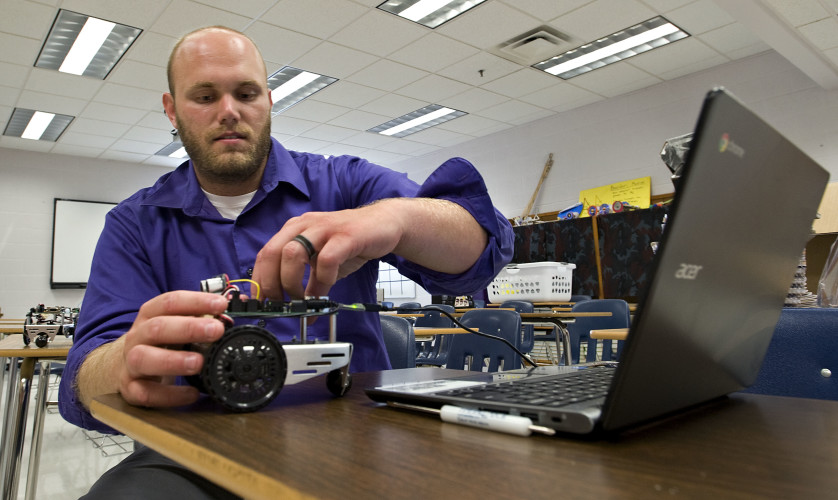 Matt Britton, physics teacher at Strasburg High School, demonstrates a computer-programmed robot that he plans to introduce to his high school's physics class this year. Britton, who also teaches statistics and geometry, participated in the  school's open house last Tuesday. Rich Cooley/Daily
