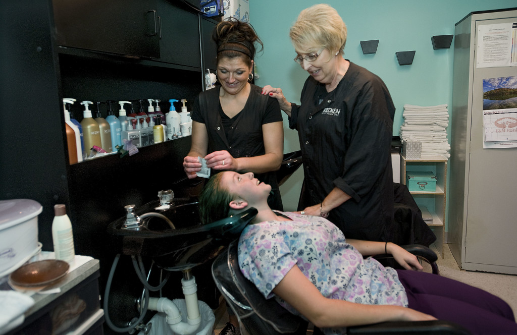 Anna Houghton, left, owner of Anna Marie Studios, washes Edinburg resident Kayla Pennington's hair on Thursday.  Houghton recently purchased her business on East High Street in Woodstock from Carolyn Foyle, longtime valley hairdresser and owner of Vivid Hair Designs and Spa.  Rich Cooley/Daily