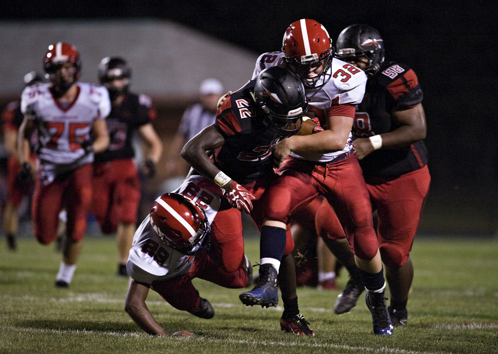 Washington's Jordan King, left, and Tyler Titus, right, try to bring down Sherando's T.J. Washington on a long run during a game earlier this season in Stephens City.   Rich Cooley/Daily