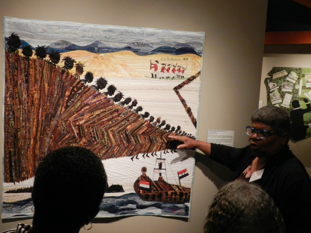 """And Still We Rise: African-American Story Quilts"" curator Carolyn Mazloomi speaks to Museum of the Shenandoah Valley visitors about the quilt ""240 Million African Slaves Ago,"" created by Valarie Pratt Poitier. Rachel Mahoney/Daily"
